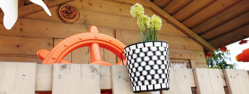 Blumentöpfe hängen am Spielturm